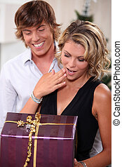 Young man giving his girlfriend a Christmas present