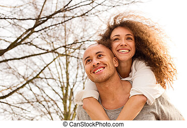 young man giving his girlfriend a piggyback