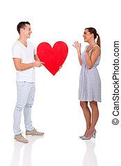 young man giving his girlfriend heart