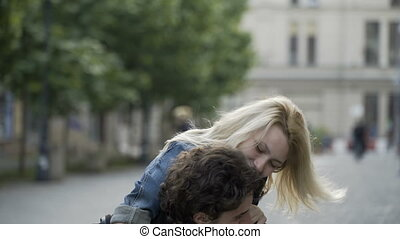 Young man giving his playful girlfriend a piggyback ride having fun and kissing outdoor