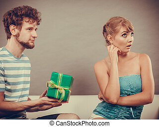 Young man giving offended woman gift box - Couple sitting on...