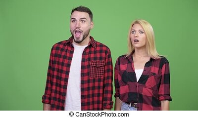Young man giving thumbs up with young woman having headache...