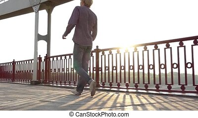 Young Man Goes Along The Bridge With a Mobile at Sunset in Slo-Mo
