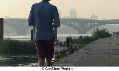 Young Man Goes Along The Dnipro Bank And Looks at His Smartphone in Slo-Mo