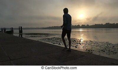 Young Man Goes Happily Along The Dnipro Riverbank at Sunset in Slo-Mo