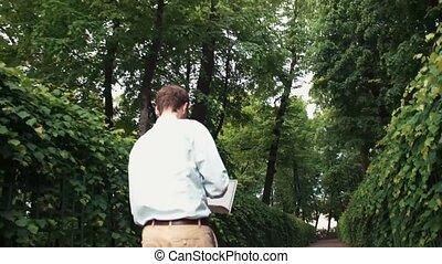 Young man going at park using laptop receiving good news and celebrating success