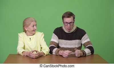 Young man going crazy with senior businesswoman looking...