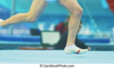 Young man gymnasts running at the gymnastics championship,...