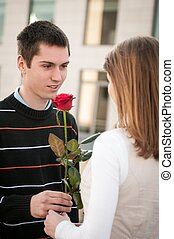 Young man handing over a flower to woman