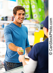 young man handing over credit card to a female cashier -...