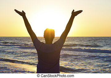 Young man hands up sunrise background blue sky and sea