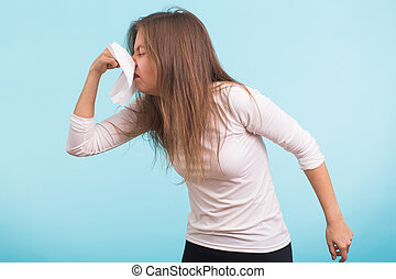 Young man has a runny nose on blue background