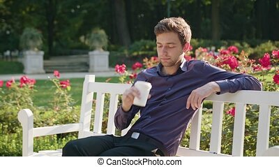 Young Man Having a Coffee in the Park