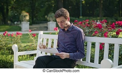 Young Man Having a Snack in the Park and Reading - A young...