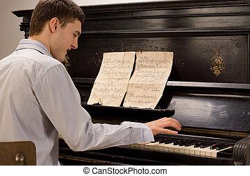 Young man having fun playing the piano