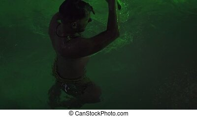 Young man having fun with shark in swimming pool at night pool party. Wet man at water party in outdoor summer night club. Night life concept.