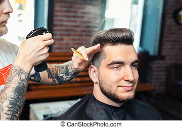Cheereful young man having hair dress, barber spraying hair with water