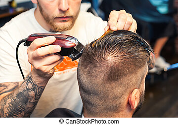 Side view of a young man having hair dress, barber working with hair clipper
