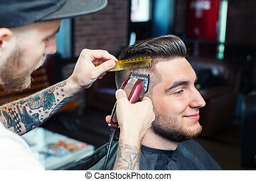 Young man having hair cutted - Side view of a young man...