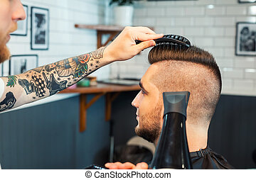 Young man having hair dress, barber working with hair dryer...