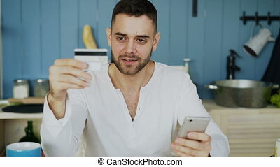 Young man having online shopping using credit card and smartphone while have breakfast in the kitchen at home