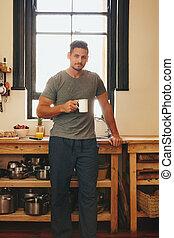 Young man having refreshing coffee in morning