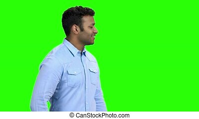 Young man having sudden back pain. Indian guy having lower back ache. Green screen background.