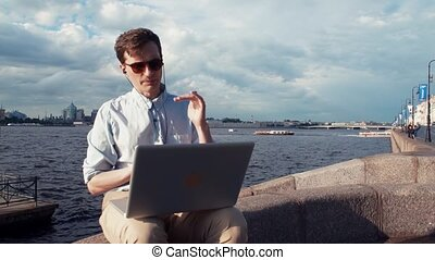 Young man having video call at laptop sitting on bench near seafront. Summer day