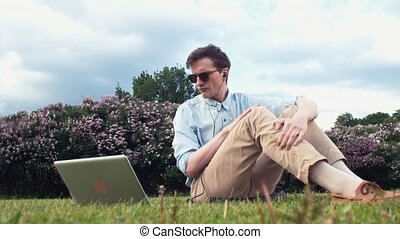 Young man having video chat at laptop sitting on green grass at park. Summer day