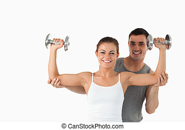 Young man helping a smiling woman to work out