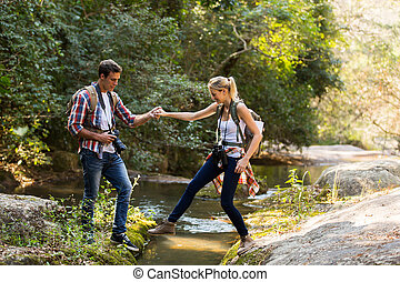 young man helping girlfriend crossing stream at mountain...
