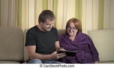 Young man Helping Her Grandmother For Using A Digital Tablet and credit card