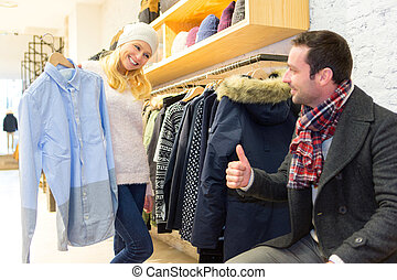 Young man helping his wife to choose clothes