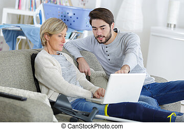 young man helping injured woman on computer