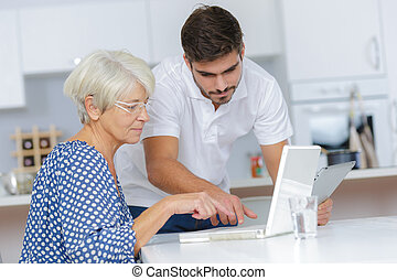 young man helping lady with her computer