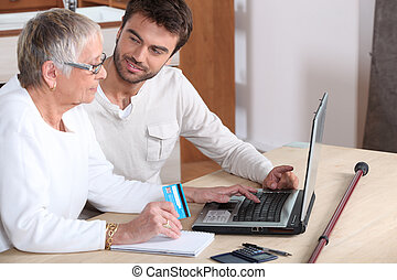 Young man helping senior woman buy online