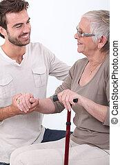 Young man helping senior woman