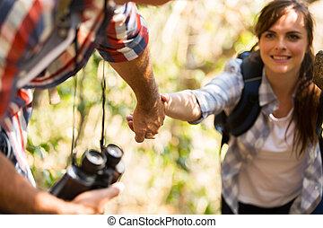 young man helping woman climbing mountain