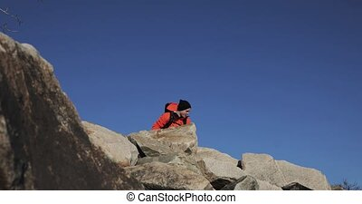 Young man hiker is happy about his ascent on the top of the cliff. Lifting his hands at the sky background.
