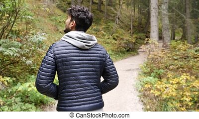 Young man hiking in lush green mountain scenery - Handsome...