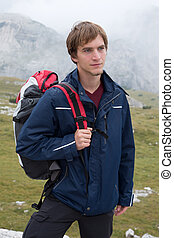 Young man hiking in the mountains with a backpack