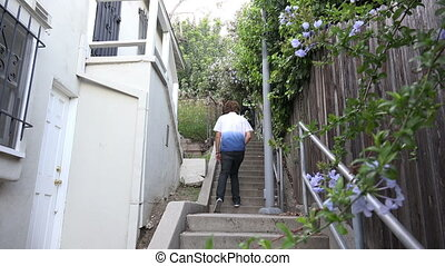 Young man hiking up a long stairway - Young multi ethnic man...