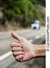 young man hitchhiking - closeup of a young caucasian man...