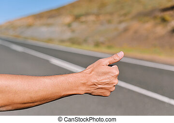 young man hitchhiking - closeup of the hand of a young...