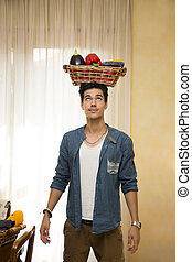Young man holding a basket of fresh vegetables on his head