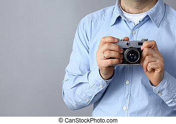 Young man holding a camera in hand.