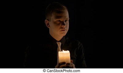 Young man holding a candle.