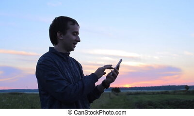 Young man holding a cellphone at sunset. He write sms