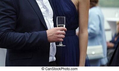 Young man holding a glass with champagne, hugging woman in blue dress outdoors at the party