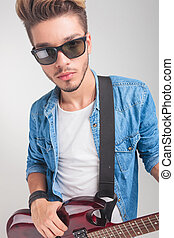 young man holding a guitar while looking at the camera
